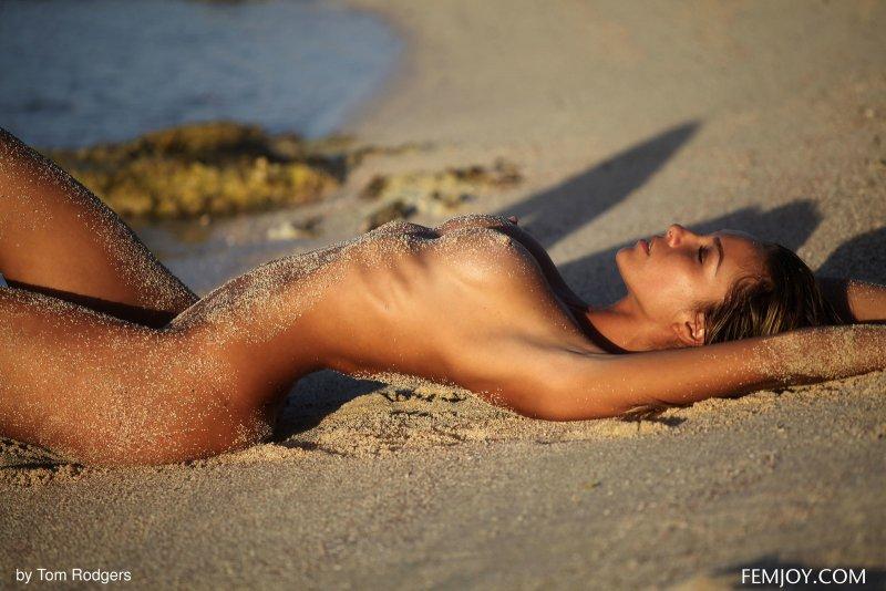 Загорелая худая модель в песке на пляже - фото