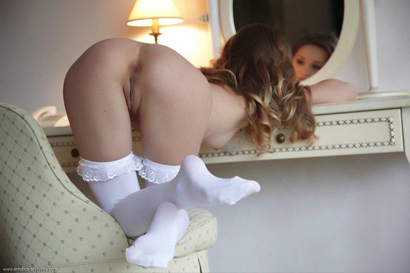 Худая девка в белых чулочках в спальне - фото