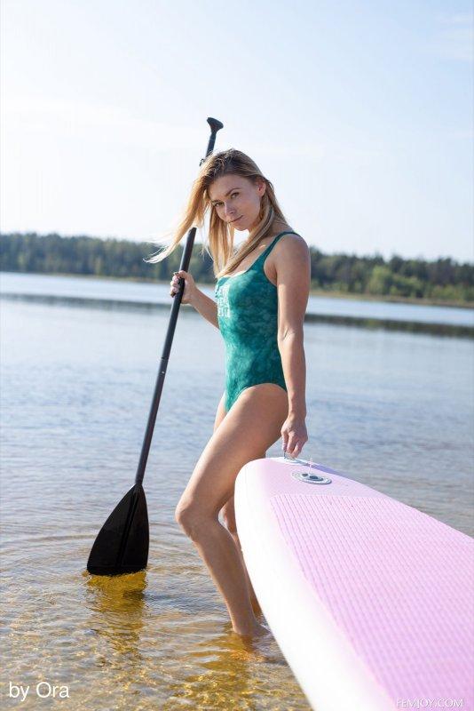 Голая отпускница плавает на доске - фото