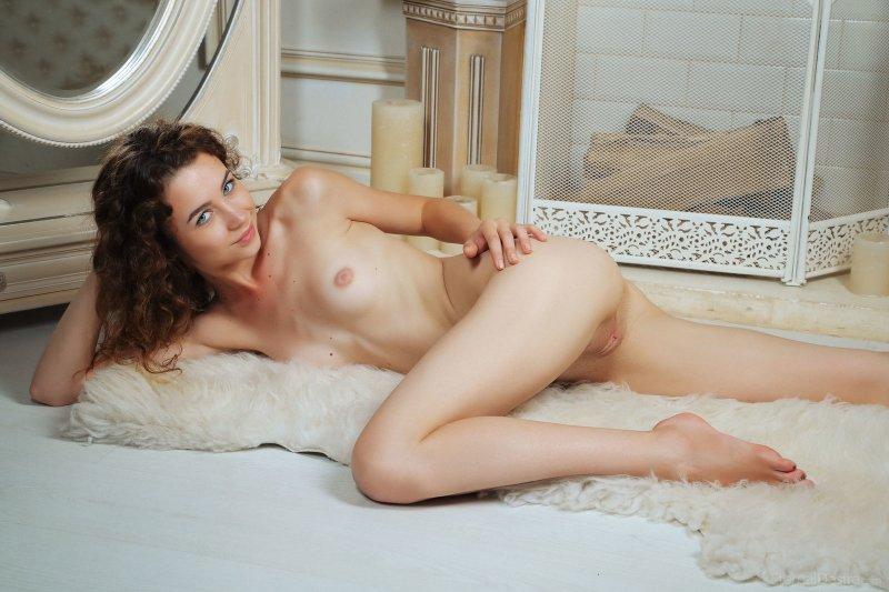Кудрявая голая девица лежит на полу - фото