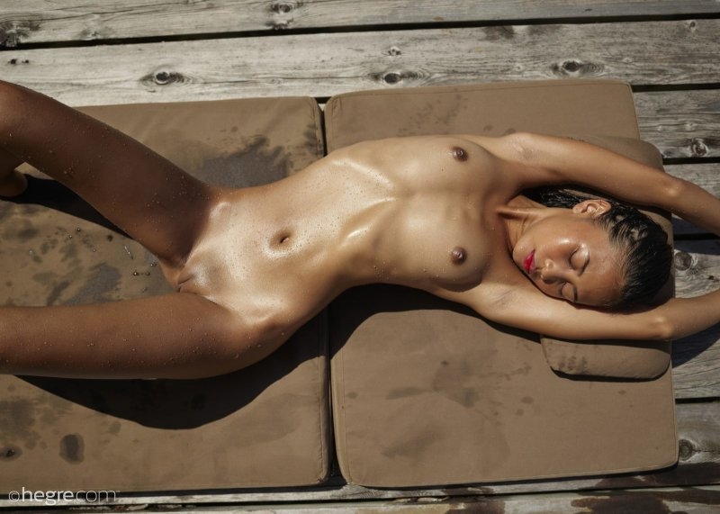 Голая азиатка загорает на пирсе - фото