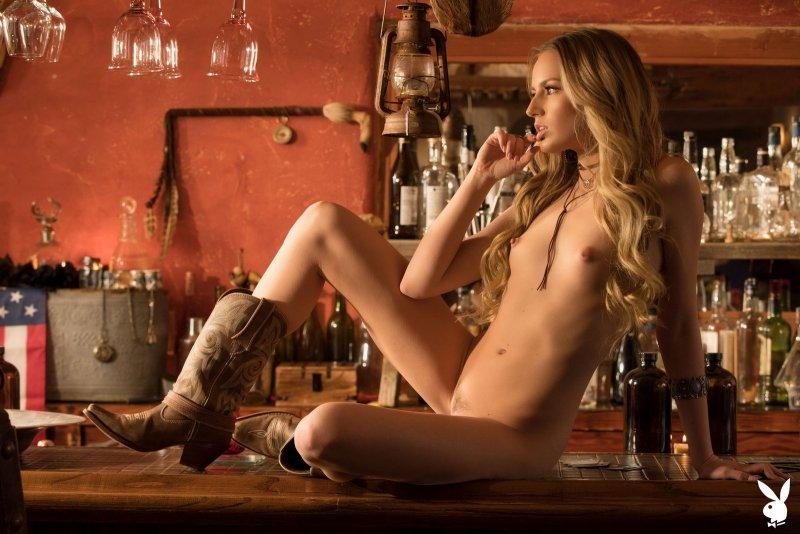 Ковбойка эротично раздевается в баре - фото