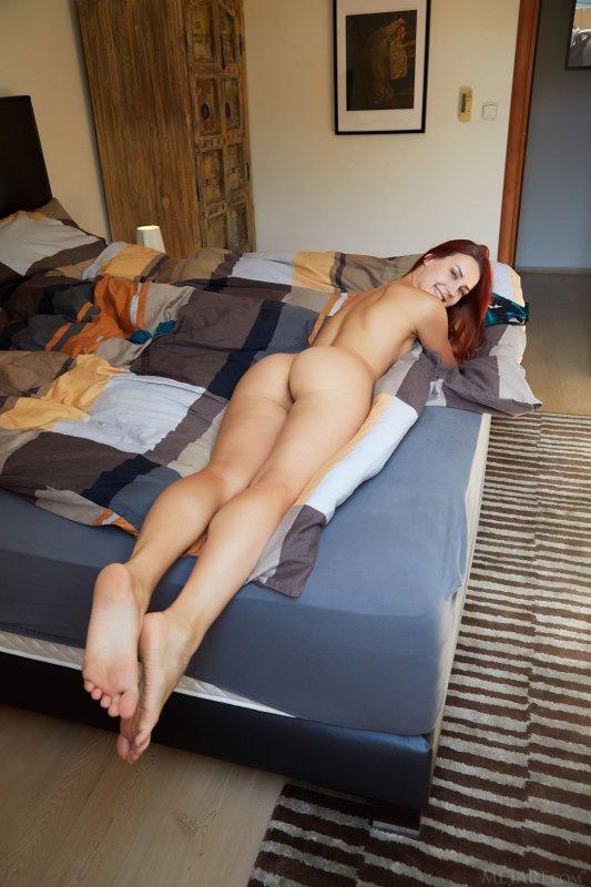 Рыжая девица разделась на кровати - фото