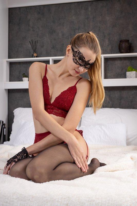 Девка в чулках и красном белье на кровати - фото