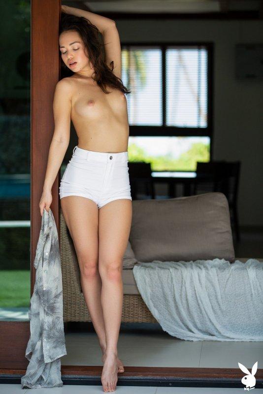 Модель в коротких шортах раздевается дома - фото