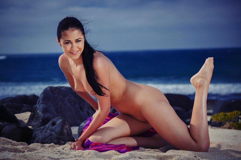 Игривая брюнетка нежится на пляже - фото