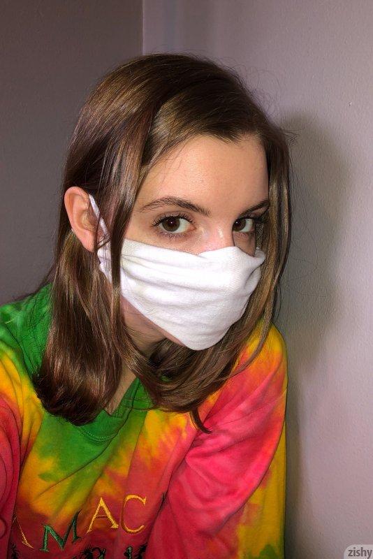 Голая девушка в маске дома на карантине - фото