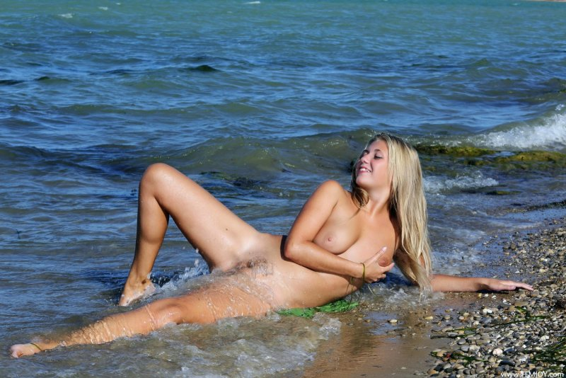 Белокурая девушка эротично купается в море - фото