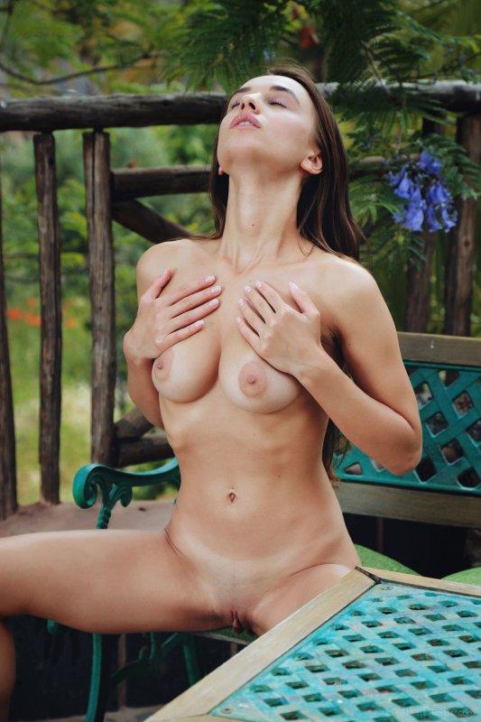 Гола девушка с красивой грудью на лавке - фото