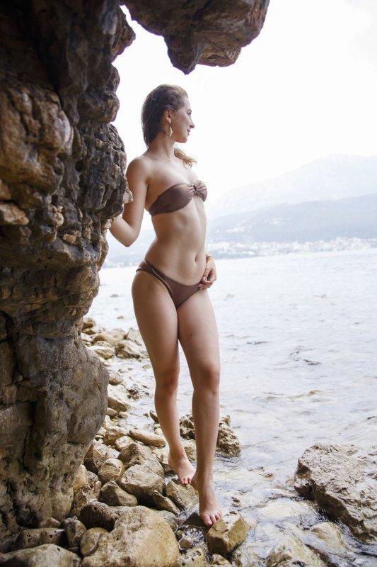 Юная сучка с красивой фигурой у моря - фото