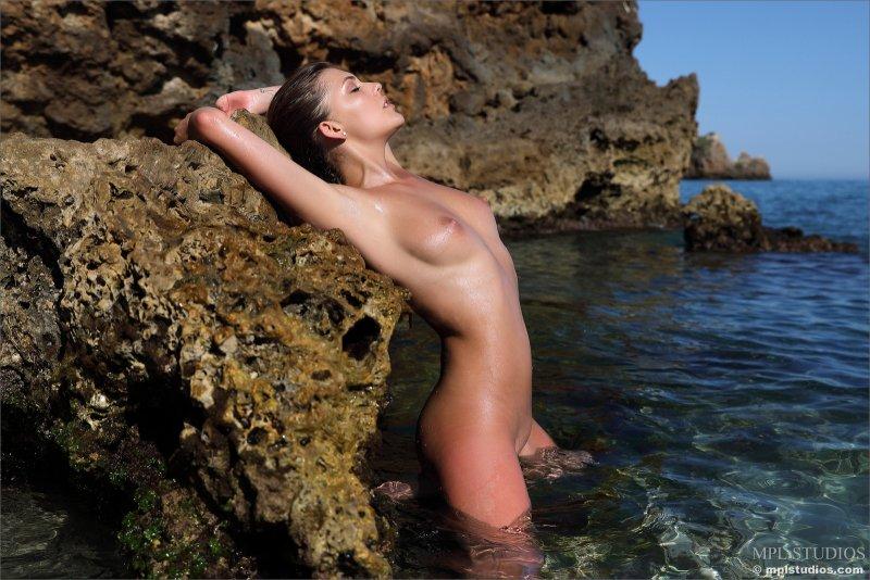 Голая нудистка купается в море - фото