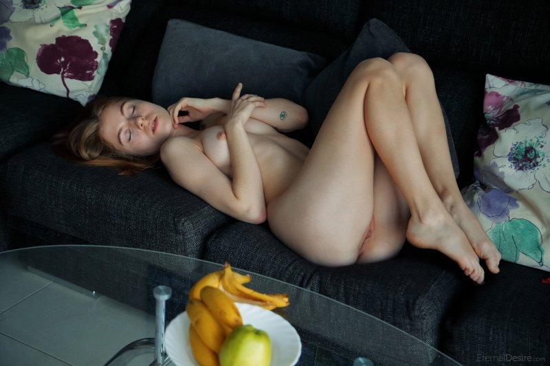 Молодая голая девкшка лежит на диване - фото