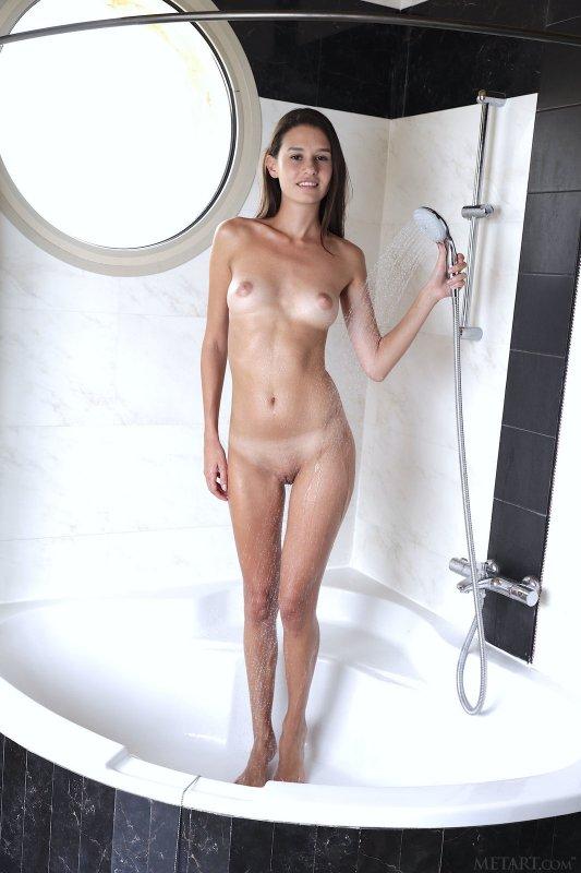Молодая красотка плескается в душе - фото
