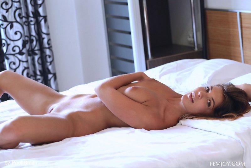 Голая девушка позирует в спальне на кровати - фото