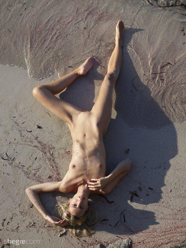 Голожопая тощая девка в песке на пляже - фото