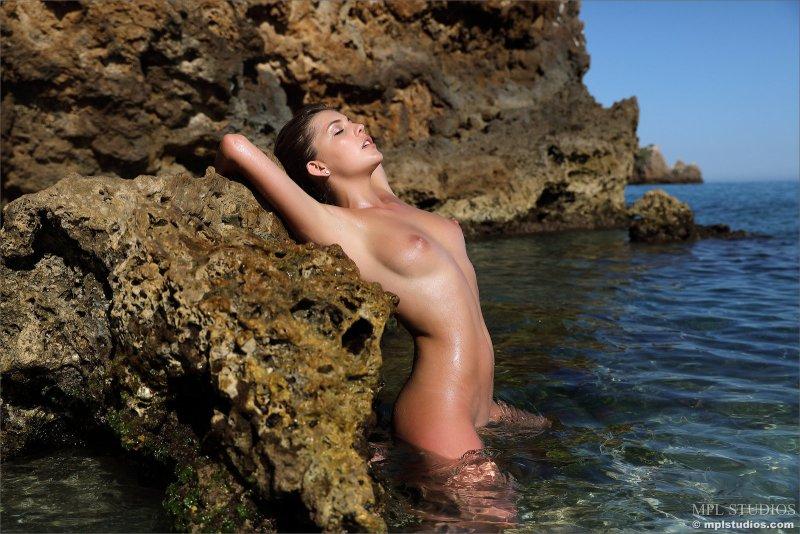 Нудистка с упругими сиськами на море - фото