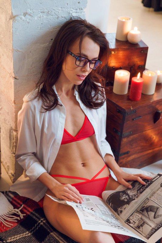 Худая девушка в очках и стрингах эротично позирует - фото