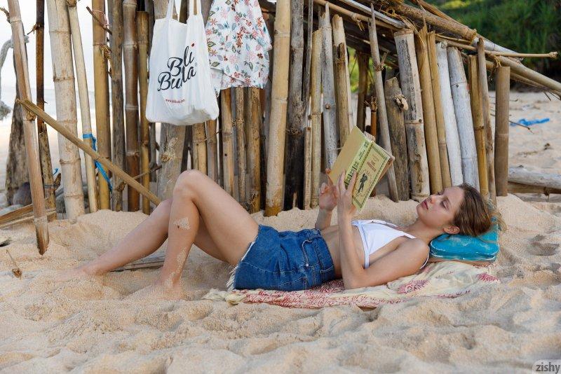 Девушка в купальнике позирует на пляже - фото