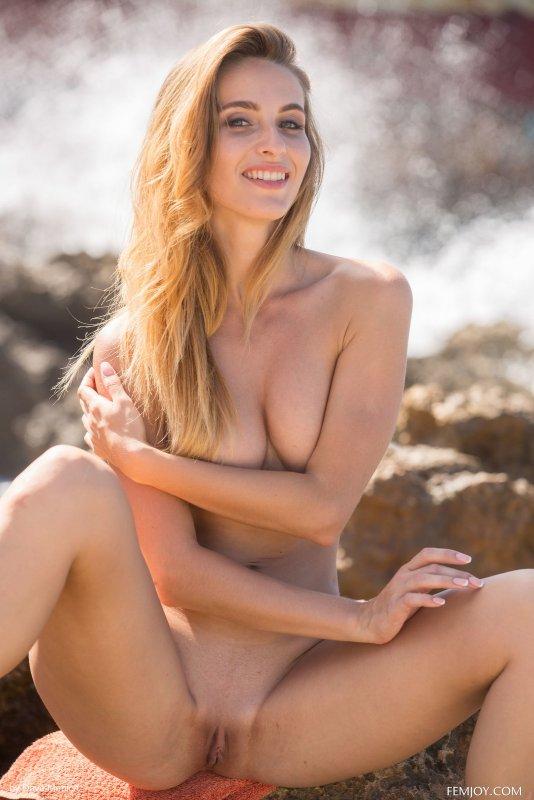 Нежная девушка эротично сняла купальник у моря - фото