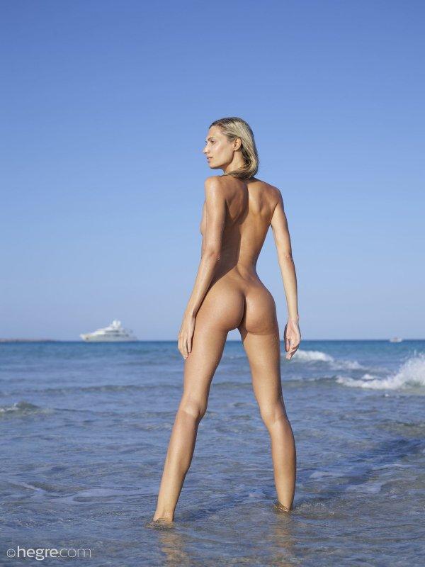 Голая длинноногая девка кайфует на пляже - фото