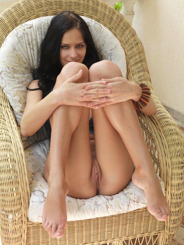 Брюнетка без трусиков раздвигает ноги на кресле - фото