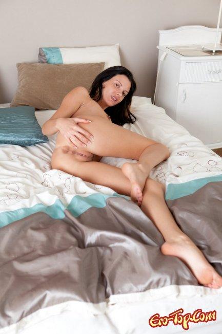 Брюнетка снимает белое бельё в кровати - фото эротика.