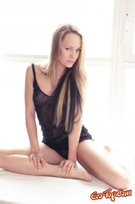 Блондинка в чёрном белье медленно раздевается. Фото эротика.